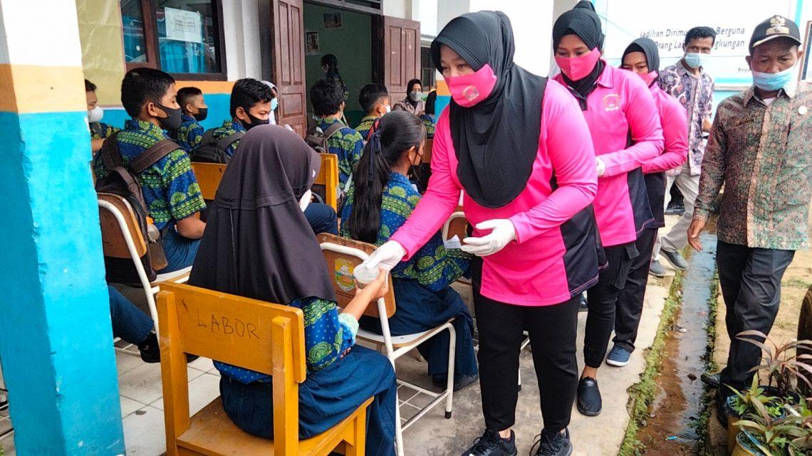 Ketua Bhayangkari Cabang Muaro Jambi, Ny. Dian Yuyan beserta anggota saat membagikan bubur kepada pelajar yang hendak divaksin. (Dok. Lamanesia.com)